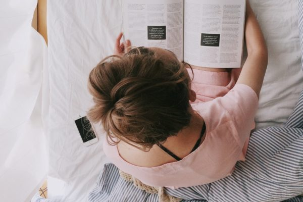 woman in pink dress sitting on bed while reading 698158 600x400 - Moms Need To Relax Too!
